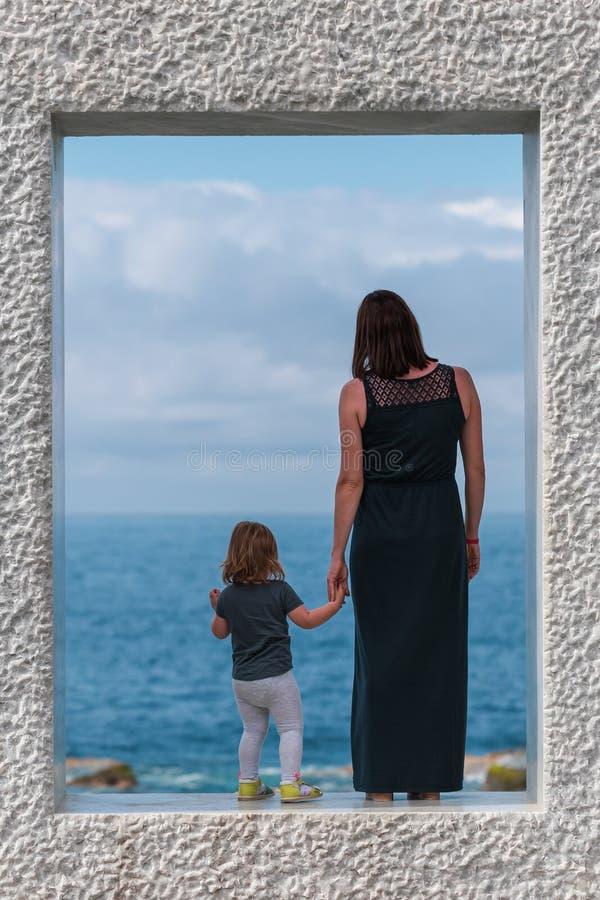 在母亲的后面看法有在大理石框架和看停留海的女儿的 库存图片