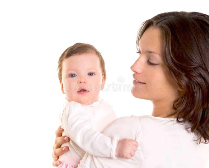 在母亲的女婴拥抱在白色武装 免版税图库摄影