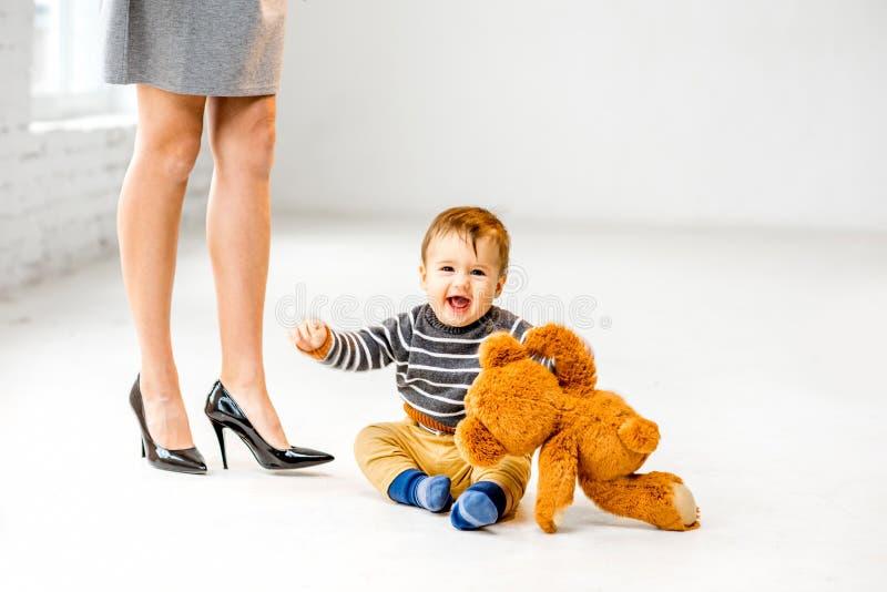 在母亲` s腿附近的男婴 库存照片