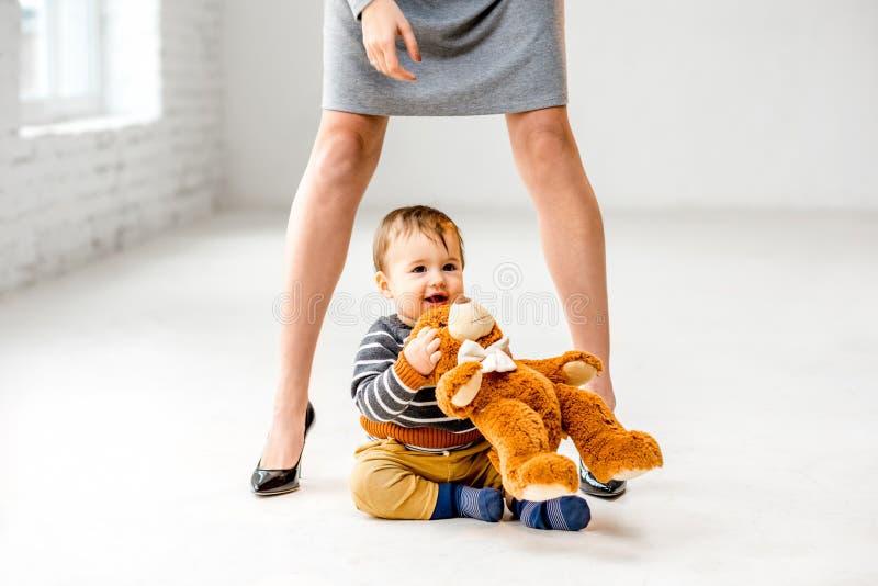 在母亲` s腿附近的男婴 免版税库存图片