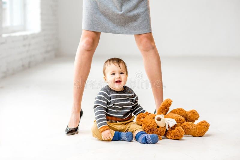在母亲` s腿附近的男婴 免版税图库摄影