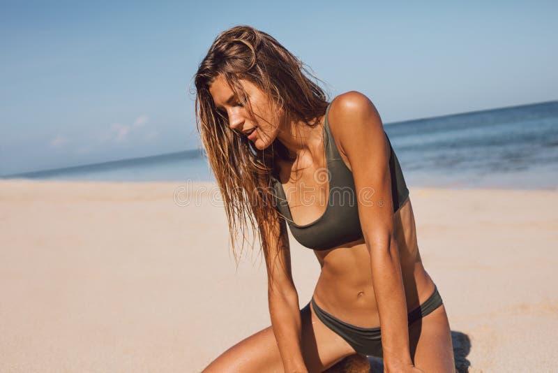 在比基尼泳装的美好的女性模型坐海滩 免版税库存图片