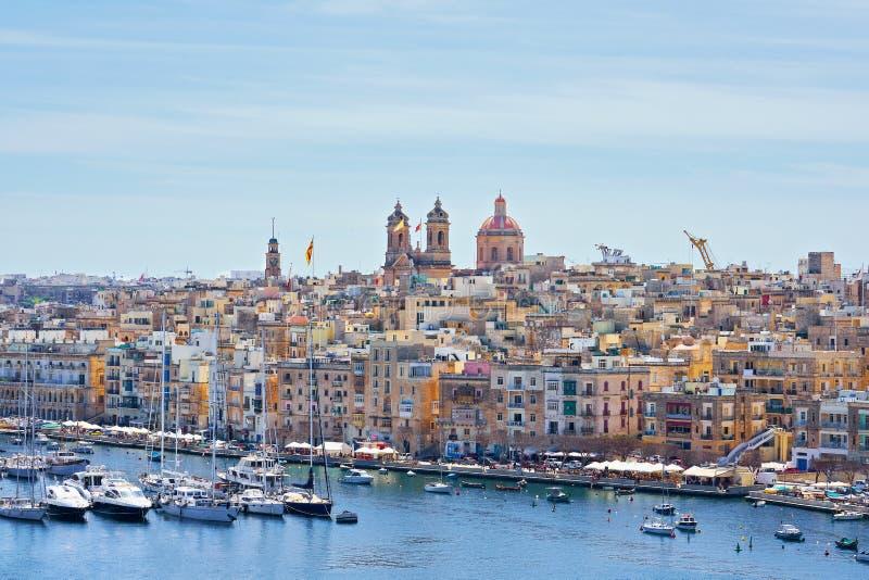 在比尔古镇江边的在海湾的全视图和地平线与五颜六色的小船在马耳他 库存照片