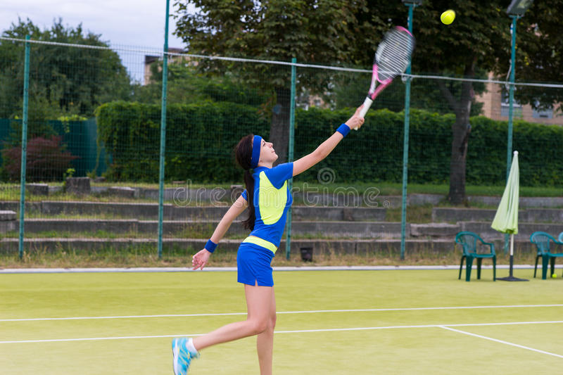 在比赛期间,女性网球员退回球 免版税库存照片