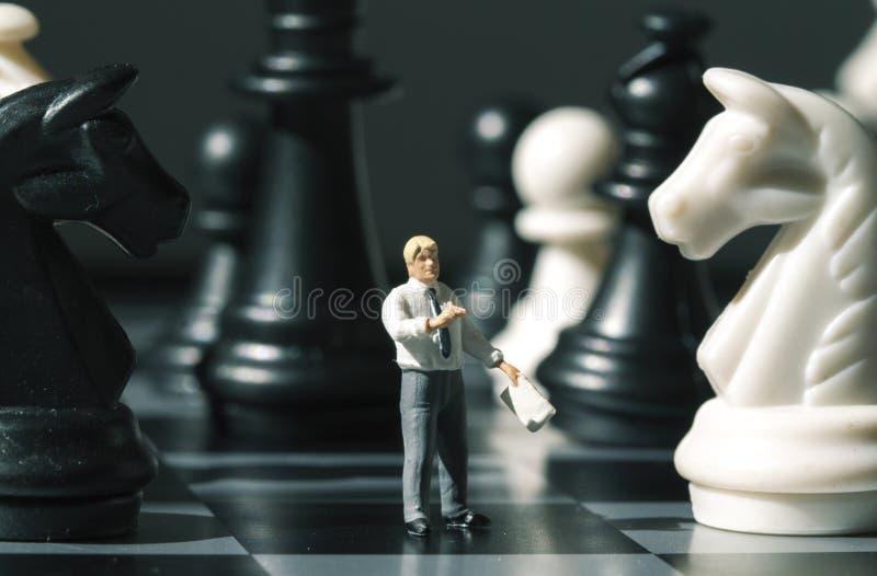 在比赛板的西洋棋棋子和棋形象 下与微型玩偶宏指令照片的棋 免版税库存照片