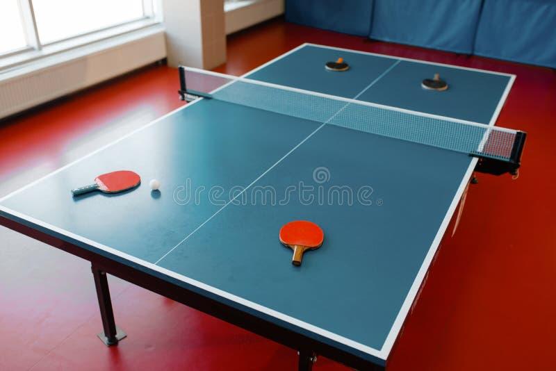 在比赛表上的乒乓球球拍与网,没人 免版税库存图片