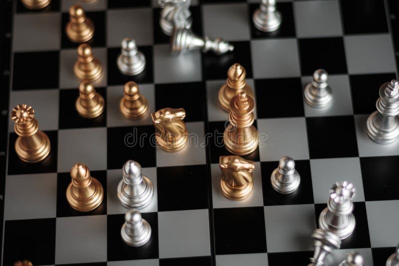 在比赛隐喻战术和事务pl的银色和金黄棋 图库摄影