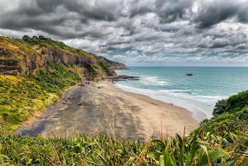 在毛利人海湾的美丽的空的黑沙子海滩在Muriwai海滩,新西兰附近 免版税图库摄影