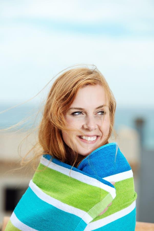 在毛巾包裹的微笑的妇女 免版税库存图片