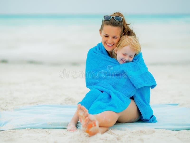 在毛巾包裹的微笑的母亲和女婴 免版税库存图片