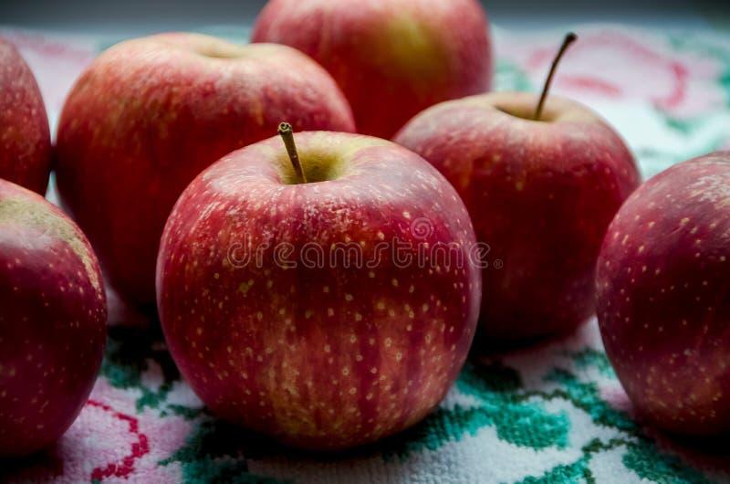 在毛巾的背景的红色苹果 免版税图库摄影