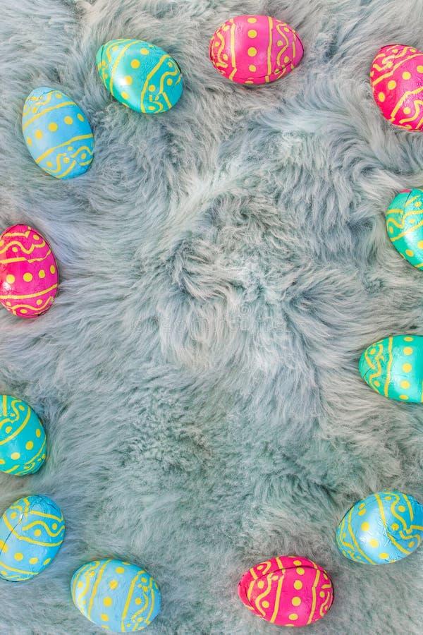 在毛皮,桃红色,蓝色和绿色鸡蛋,复活节backgroung的多个色的复活节彩蛋 免版税库存图片