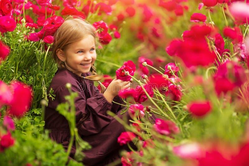 在毛茛中明亮的春天花的快乐的女孩  免版税库存图片