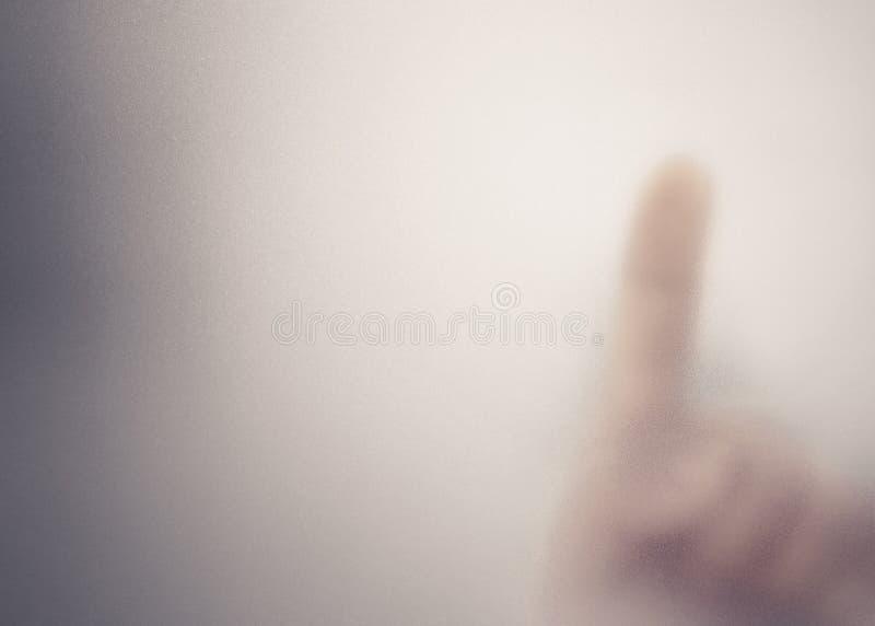 在毛玻璃后的手指 免版税库存图片