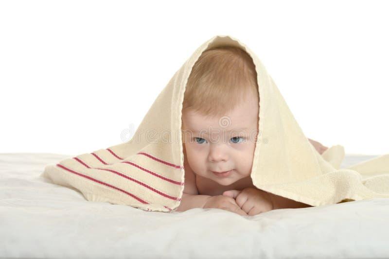 在毯子下的可爱的男婴 图库摄影