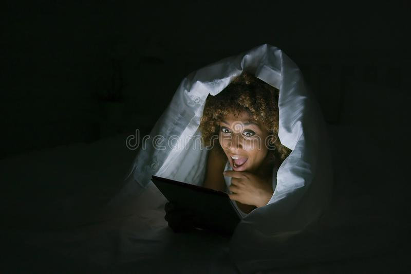 在毯子下的激动的妇女有片剂的 库存图片