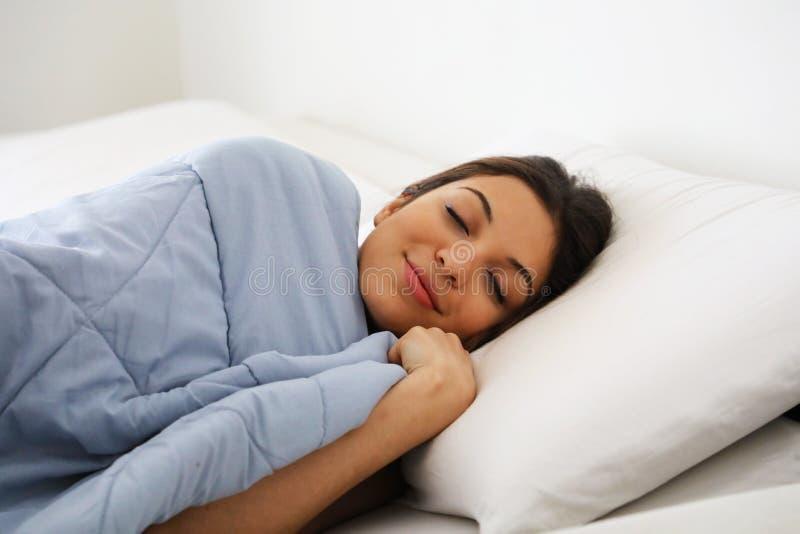 在毯子下的画象相当少妇在现代公寓早晨 她保持眼睛闭上并且看起来满意 免版税库存照片