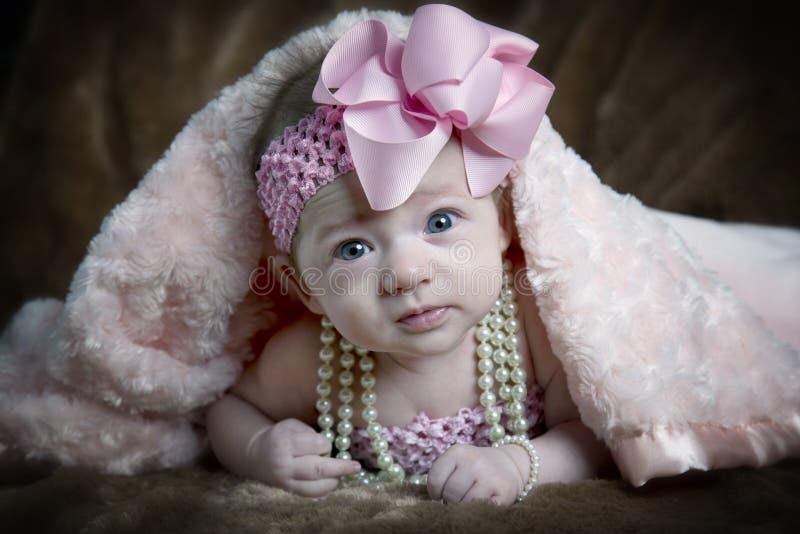 在毯子之下的逗人喜爱的小女孩 免版税图库摄影