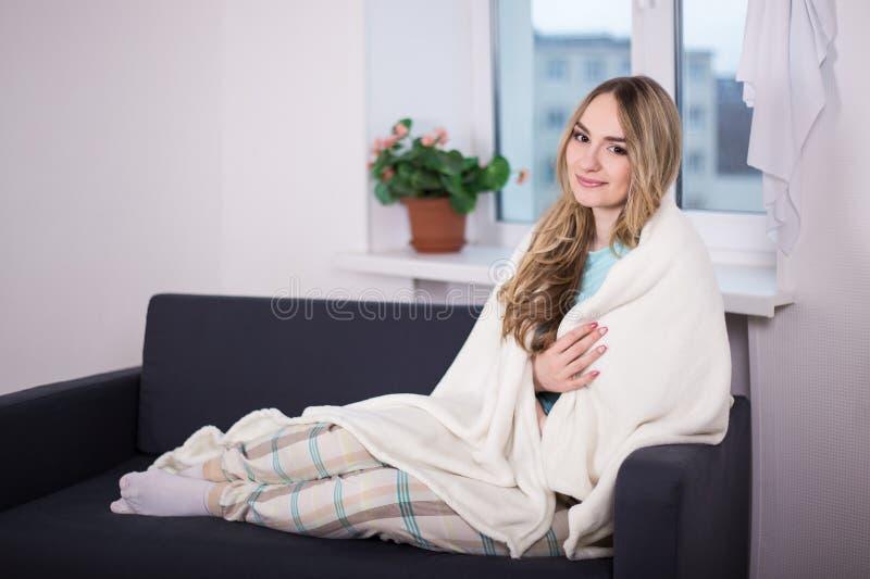 在毯子包裹的睡衣的少妇坐在客厅 库存图片