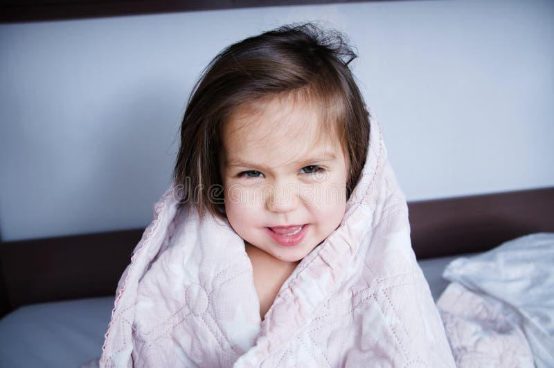 在毯子包裹的逗人喜爱的微笑的小孩去睡坐床 在国内生活方式的睡眠日程表 愉快可爱 库存照片