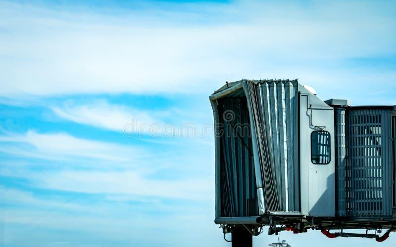 在民航以后的喷气机桥梁在机场离开反对天空蔚蓝和白色云彩 飞机乘客搭乘桥梁 免版税图库摄影