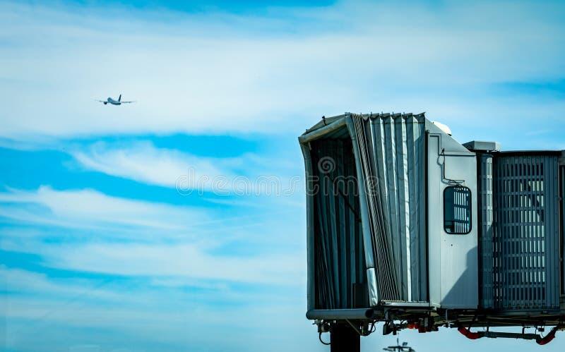 在民航以后的喷气机桥梁离开在机场和平面飞行在天空蔚蓝和白色云彩 ?? 免版税库存照片