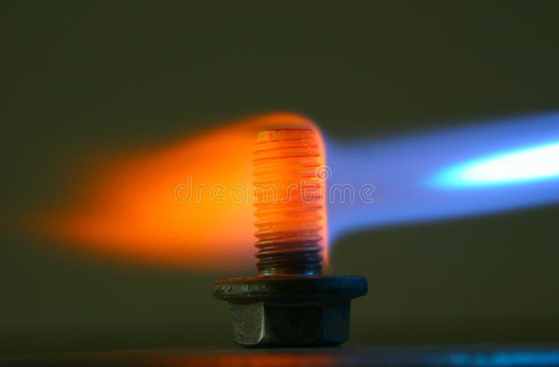在气体火炬的火焰的生锈的螺栓 库存照片