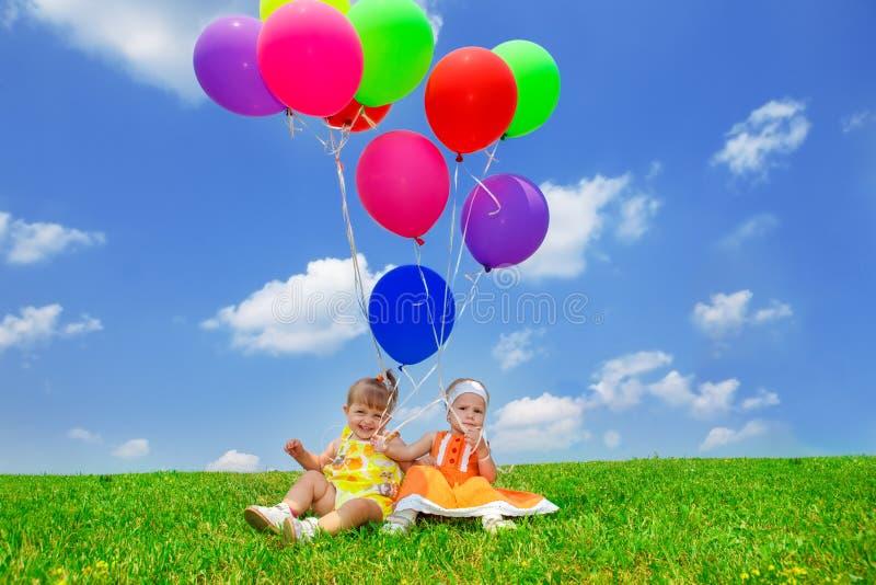 在气球下的小孩朋友 库存图片