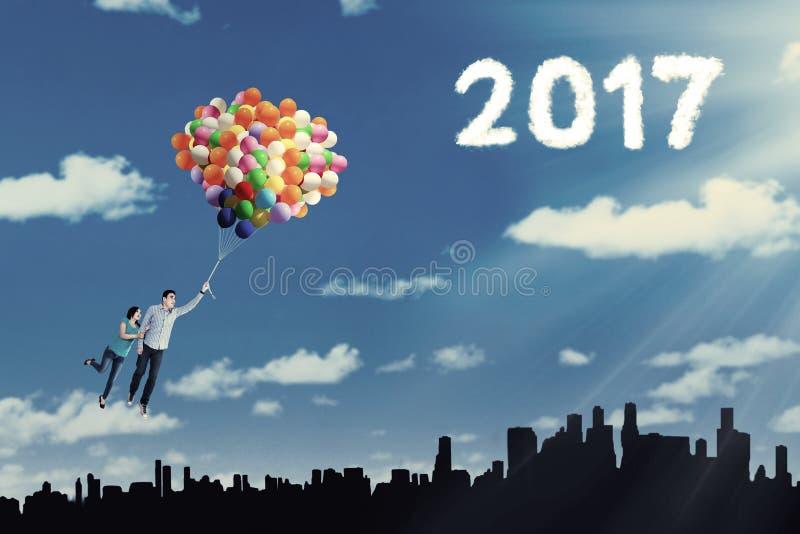 在气球的年轻夫妇飞行 免版税库存照片