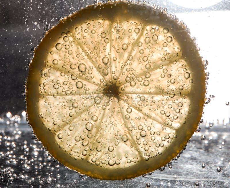 在水下的柠檬切片与泡影 图库摄影