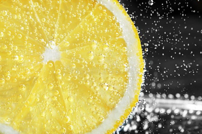在水下的柠檬切片与泡影 免版税图库摄影