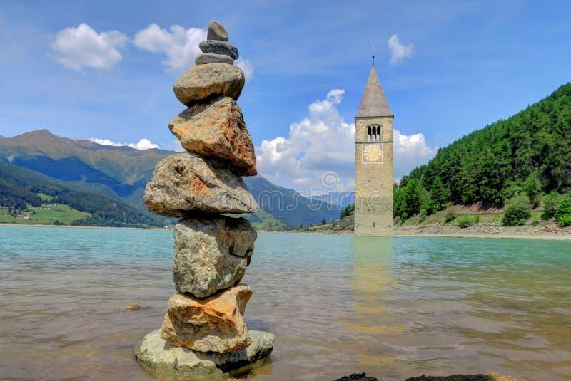 在水下的高耸附近晃动石标在Reschensee湖, Ital 免版税图库摄影