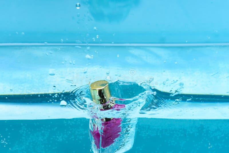 在水与透明泡影和水下的指甲油瓶飞溅,蓝色背景 指甲油落入纯净 免版税图库摄影