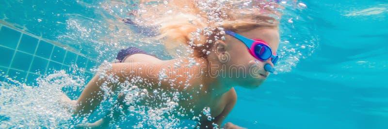 在水公园游泳水下和微笑的横幅,长的格式的女孩 图库摄影