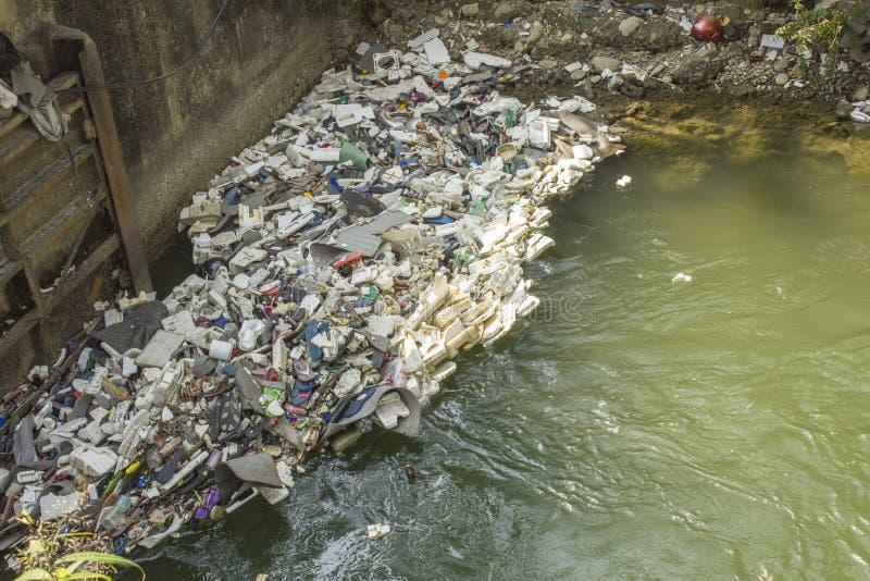 在水坝的各种各样的塑料和橡胶垃圾在河 生态灾变 库存照片