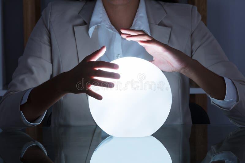 在水晶球的女实业家手 库存图片
