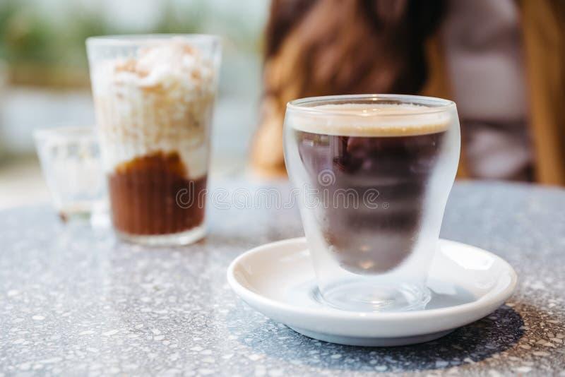 在水杯的泡沫的硝基冷的酿造咖啡在花岗岩上面桌上有迷离背景 免版税图库摄影