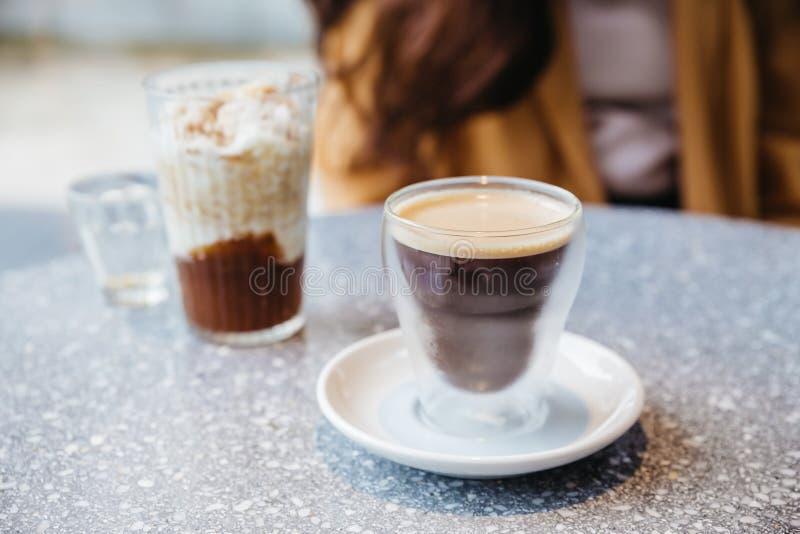 在水杯的泡沫的硝基冷的酿造咖啡在花岗岩上面桌上有迷离背景 免版税库存照片
