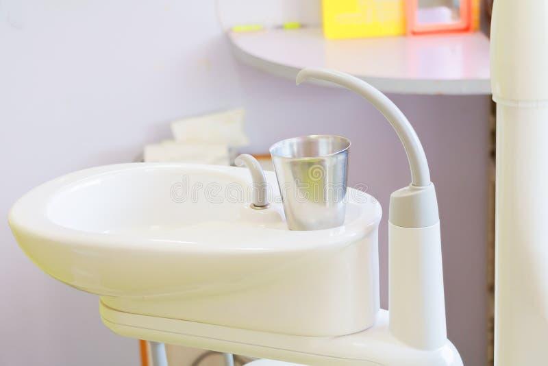 在水槽医疗设备牙医关闭,陶瓷痰盂和水补白的玻璃铬在诊所 库存图片