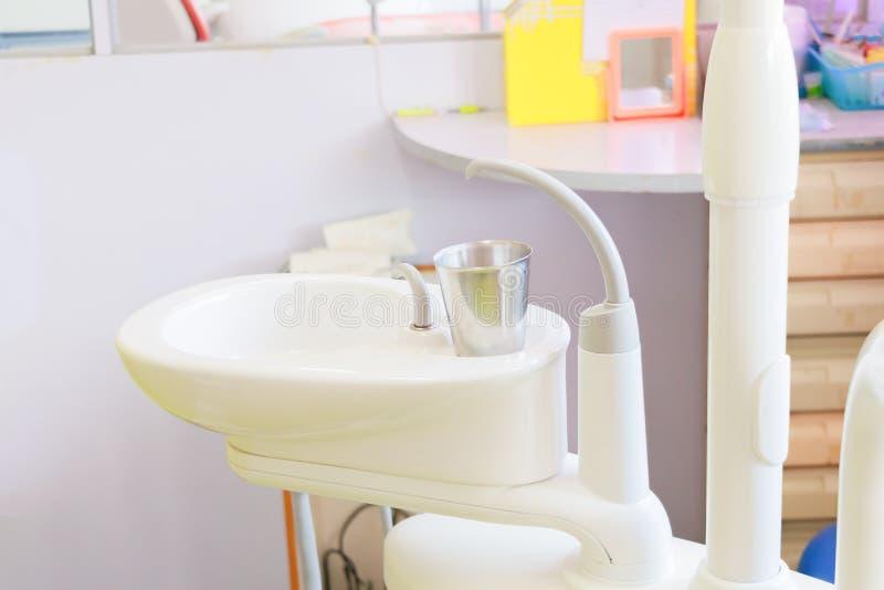 在水槽医疗设备牙医关闭,陶瓷痰盂和水补白的玻璃铬在诊所 免版税库存照片