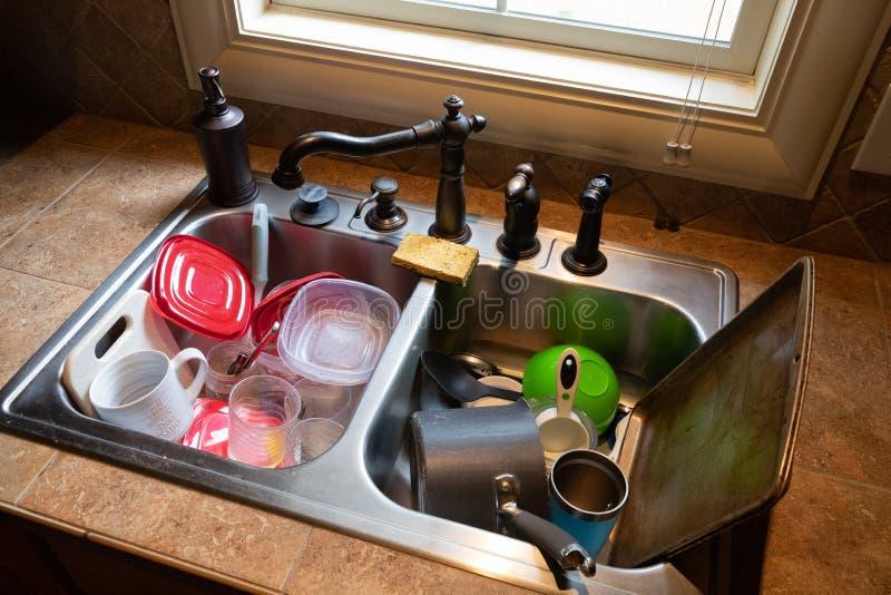 在水槽堆积的肮脏的盘 免版税库存照片