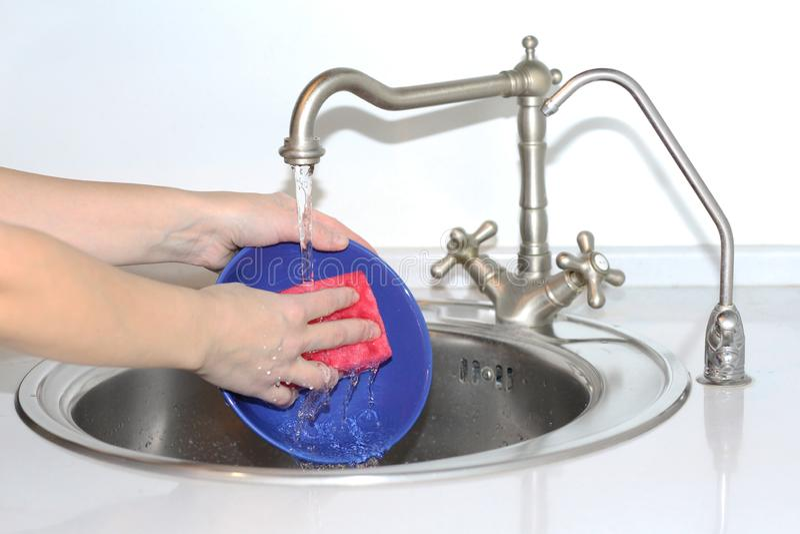在水槽的妇女洗涤的盘 她有一块清洗的海绵在她的手 免版税库存照片
