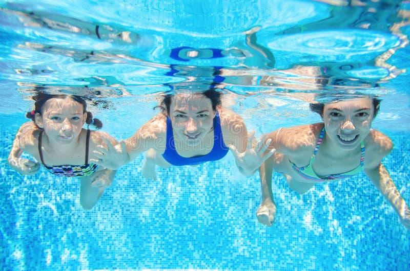 在水池水中、愉快的活跃母亲和孩子的家庭游泳获得乐趣在水、健身和体育下与孩子 库存图片