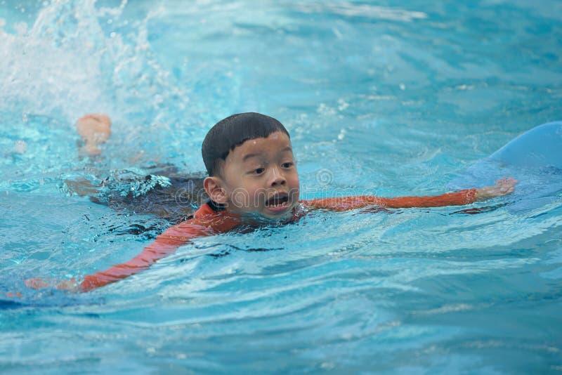 在水池的亚洲男孩游泳 库存照片