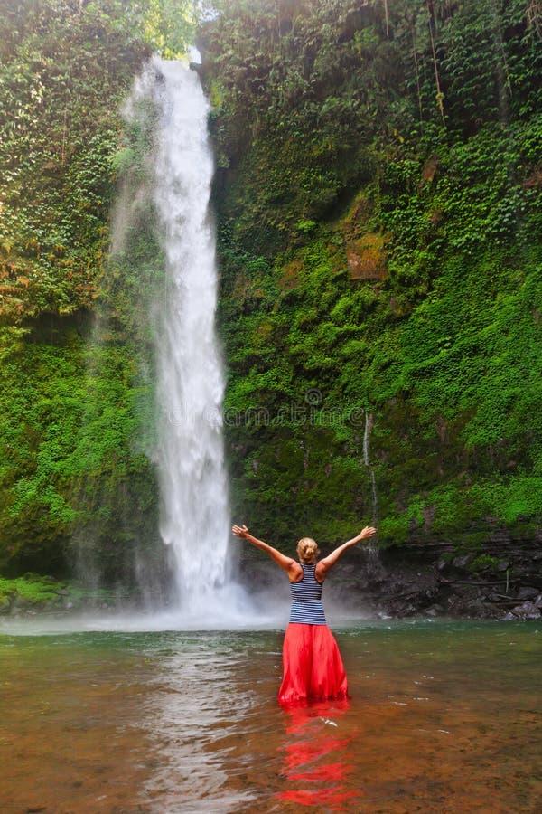 在水池的妇女立场在瀑布下,在落的水看见 免版税库存图片