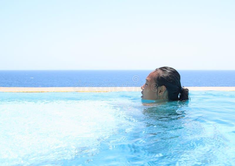 在水池的年轻女人游泳由海 免版税库存照片