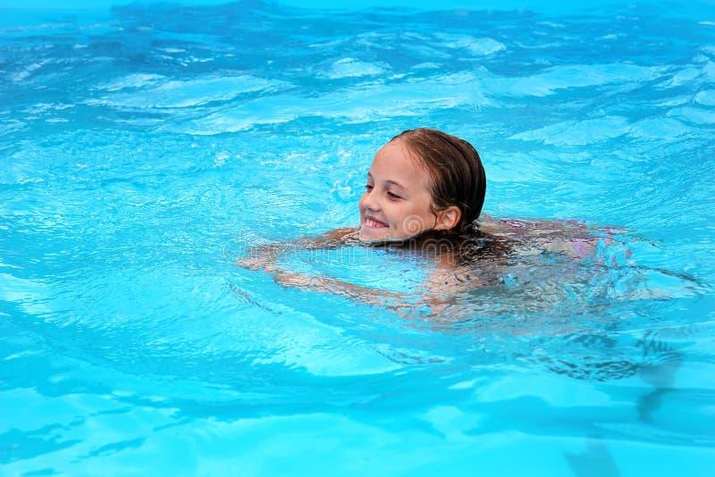 在水池的微笑的女孩游泳 免版税图库摄影