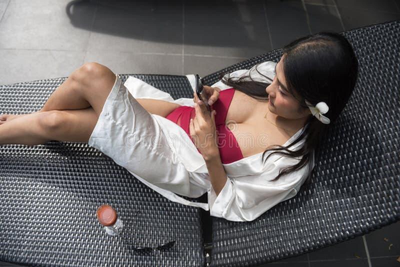 在水池的性感的亚洲妇女戏剧智能手机 免版税库存照片