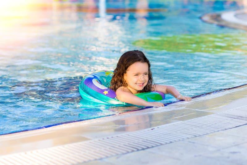 在水池的愉快的女孩游泳与可膨胀的圆环在一个晴朗的夏日 孩子学会游泳 r 免版税图库摄影