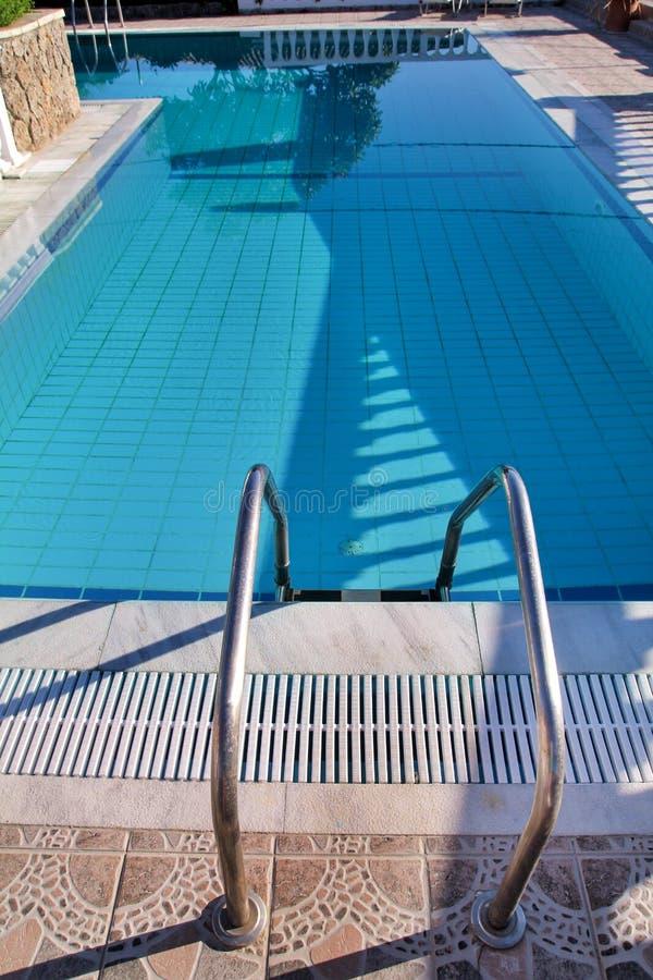 在水池的扶手栏杆 有台阶的游泳场在热带手段 水池扶手栏杆视图 有晴朗的反射的水游泳场 免版税图库摄影